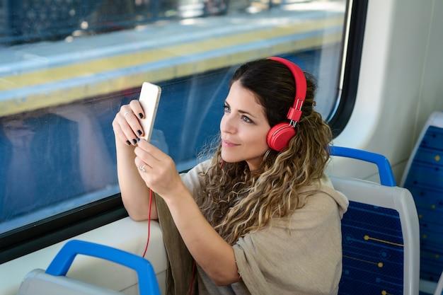 Jonge vrouw die een selfie op trein met haar telefoon neemt.