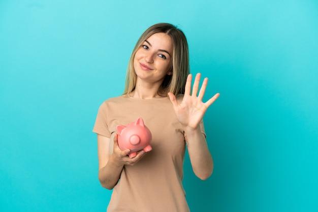 Jonge vrouw die een spaarpot over geïsoleerde blauwe achtergrond houdt die vijf met vingers telt