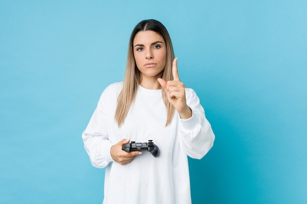 Jonge vrouw die een spelcontrolemechanisme houdt dat nummer één met vinger toont