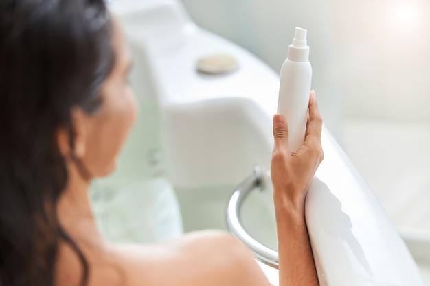 Jonge vrouw die een spuitfles met lotion vasthoudt terwijl ze in bad gaat