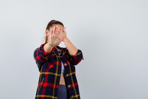 Jonge vrouw die een stopgebaar toont, de ogen bedekt met de hand in de crop-top, een geruit hemd en er serieus uitziet. vooraanzicht.