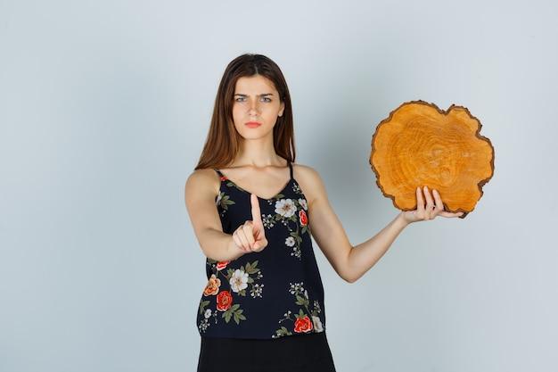 Jonge vrouw die een stuk hout vasthoudt, een klein gebaar in blouse, rok laat zien en er serieus uitziet, vooraanzicht.