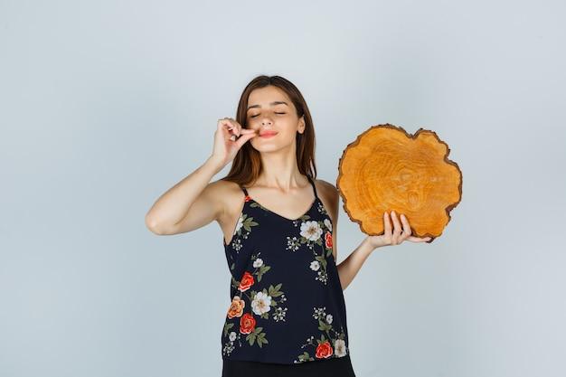 Jonge vrouw die een stuk hout vasthoudt, een smakelijk gebaar in een blouse laat zien en er opgetogen uitziet. vooraanzicht.