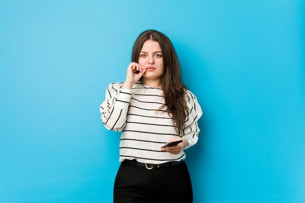 Jonge vrouw die een telefoon met vingers op lippen houdt die een geheim houden.