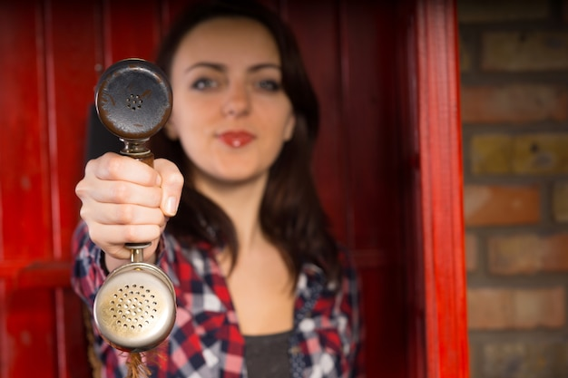 Jonge vrouw die een telefoonhoorn voorstelt aan de kijker in haar uitgestrekte hand met focus op de ontvanger