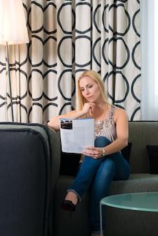 Jonge vrouw die een tijdschrift in hotelruimte leest