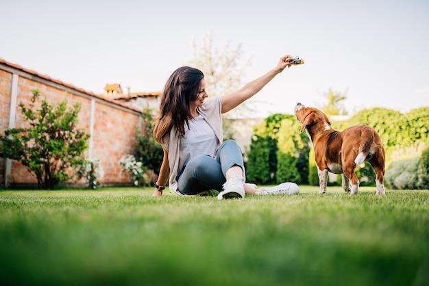 Jonge vrouw die een traktatie geeft aan haar hond in de tuin.