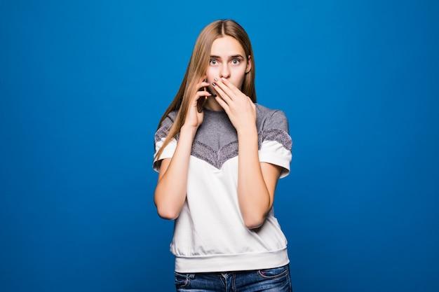 Jonge vrouw die een verraste gezichtsuitdrukking heeft terwijl het spreken op de telefoon