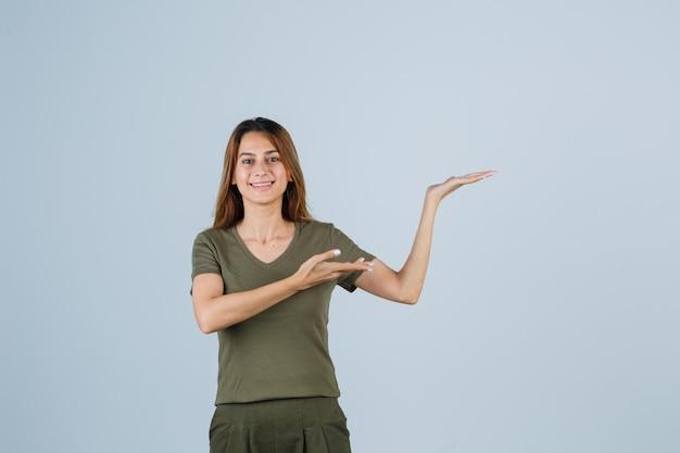 Jonge vrouw die een verwelkomend gebaar in t-shirt, broek toont en er gelukkig uitziet, vooraanzicht.
