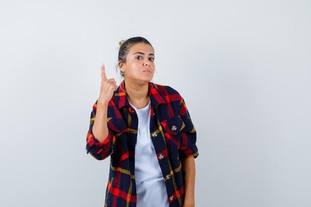 Jonge vrouw die één vinger in geruit overhemd toont en nieuwsgierig kijkt, vooraanzicht.