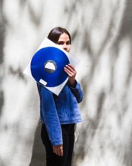 Jonge vrouw die een vinylverslag houdt