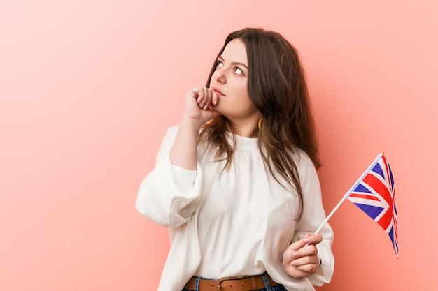 Jonge vrouw die een vlag houdt van het verenigd koninkrijk zijdelings kijkend met twijfelachtige en sceptische uitdrukking.