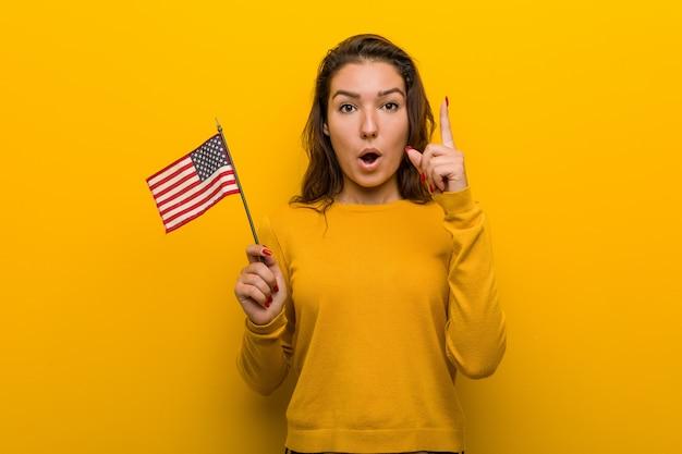 Jonge vrouw die een vlag houdt van verenigde staten die één of ander groot idee, concept creativiteit hebben.