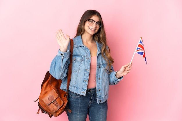 Jonge vrouw die een vlag van het verenigd koninkrijk houdt die op roze muur wordt geïsoleerd die met hand met gelukkige uitdrukking groet