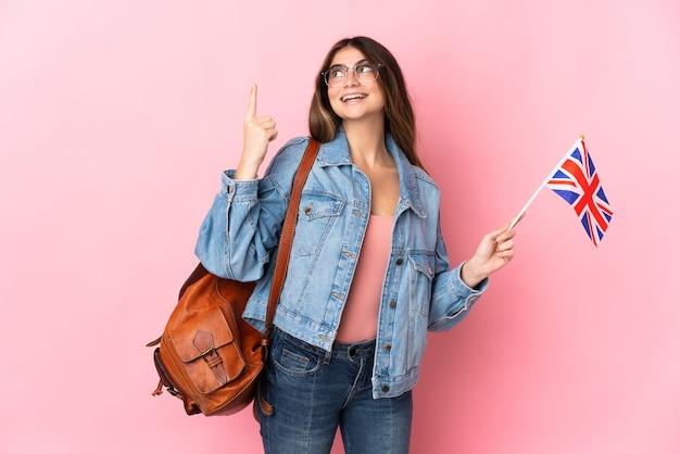 Jonge vrouw die een vlag van het verenigd koninkrijk op roze houdt die een geweldig idee benadrukt