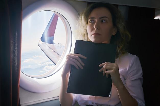 Jonge vrouw die een vliegtuigpassagier is, ervaart aerofobie