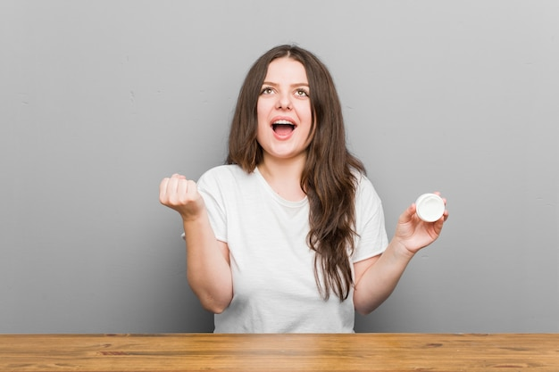 Jonge vrouw die een vochtinbrengende crème houdt die onbezorgd en opgewekt toejuicht. overwinning concept.