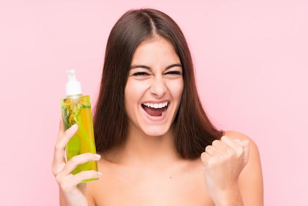 Jonge vrouw die een vochtinbrengende crème met aloë vera houdt zorgeloos en opgewonden toejuichend