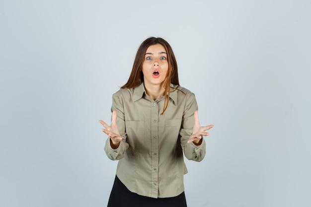 Jonge vrouw die een vraaggebaar maakt in shirt, rok en geschokt kijkt. vooraanzicht.