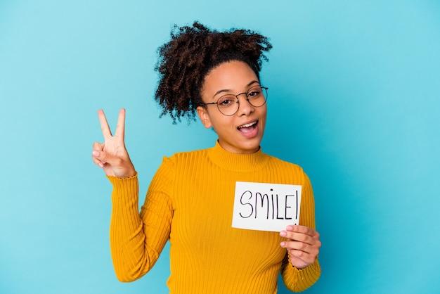 Jonge vrouw die een vreugdevol en zorgeloos glimlachconcept houdt dat een vredessymbool met vingers toont