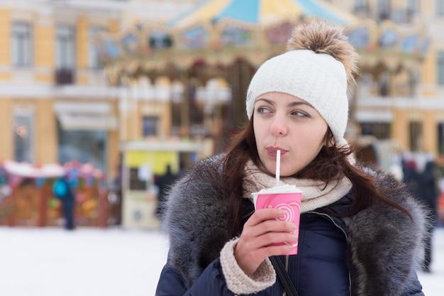 Jonge vrouw die een warme cappuccino drinkt tijdens een winterevenement of festival dat buiten op een besneeuwd stadsplein staat in haar warme wintermode