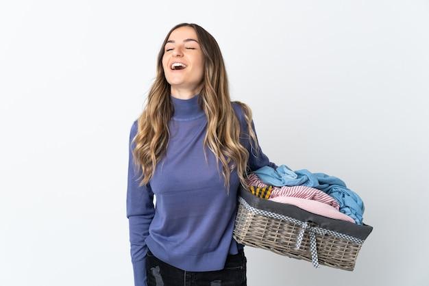 Jonge vrouw die een wasmand houdt die bij muur het lachen wordt geïsoleerd