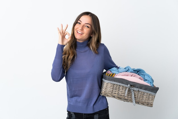 Jonge vrouw die een wasmand houdt die op muur wordt geïsoleerd die ok teken met vingers toont