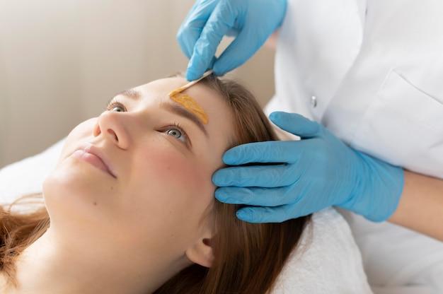 Jonge vrouw die een wenkbrauwbehandeling krijgt bij de schoonheidssalon