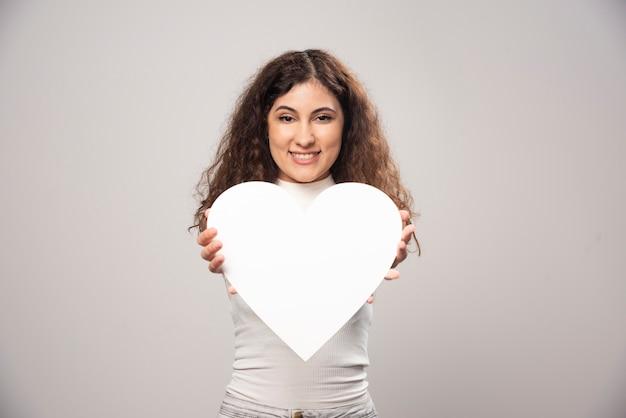 Jonge vrouw die een wit met de hand gemaakt document hart geeft. hoge kwaliteit foto