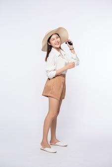 Jonge vrouw die een wit overhemd en korte broek draagt, een hoed draagt en een handvat op de hoed