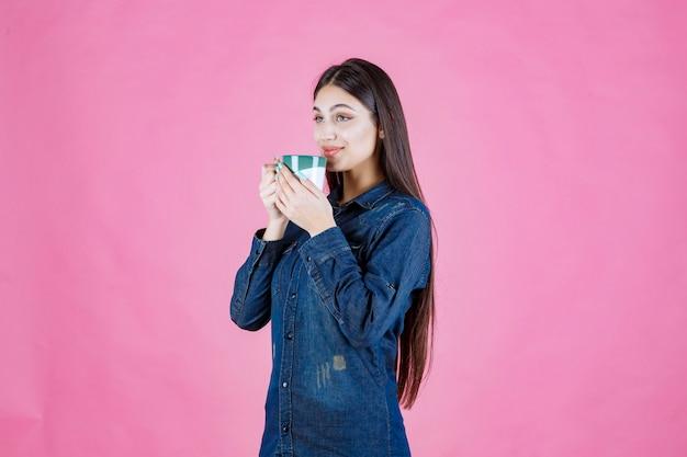 Jonge vrouw die een witgroene koffiemok houdt en ruikt