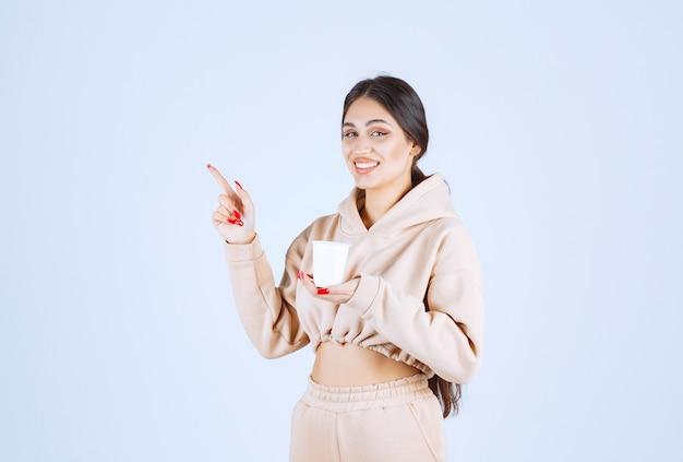 Jonge vrouw die een witte koffiekop vasthoudt en links iemand laat zien