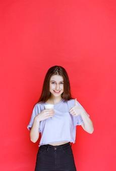 Jonge vrouw die een witte wegwerpwaterkop houdt en tevredenheidsteken toont.