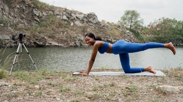 Jonge vrouw die een yoga onderwijst stelt buiten