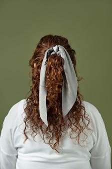 Jonge vrouw die een zakdoek draagt als haartoebehoren