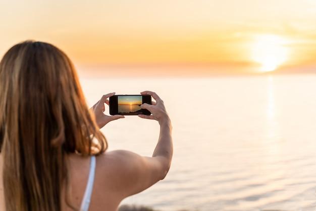 Jonge vrouw die een zonsondergang op het strand met haar mobiele telefoon fotografeert