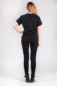 Jonge vrouw die een zwart t-shirt met korte mouwen draagt en tegen een witte muur staat