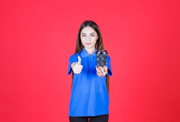 Jonge vrouw die een zwarte wegwerpkoffiekop houdt en positief handteken toont