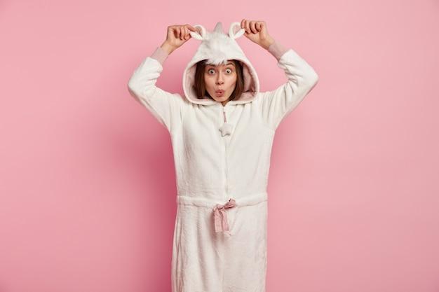 Jonge vrouw die eenhoornpyjama's draagt