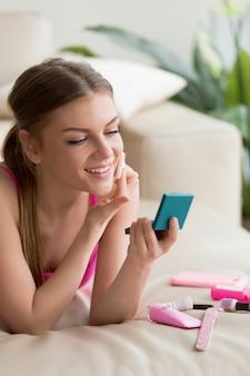 Jonge vrouw die eenvoudige dagelijkse make-up thuis maakt