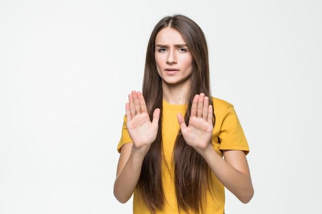Jonge vrouw die eindegebaar met haar hand maakt die op een witte muur wordt geïsoleerd