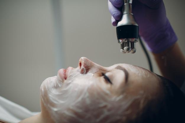 Jonge vrouw die elektrische rf-opheffende gezichtsmassage ontvangt bij beauty spa met elektroporatie-apparatuur.