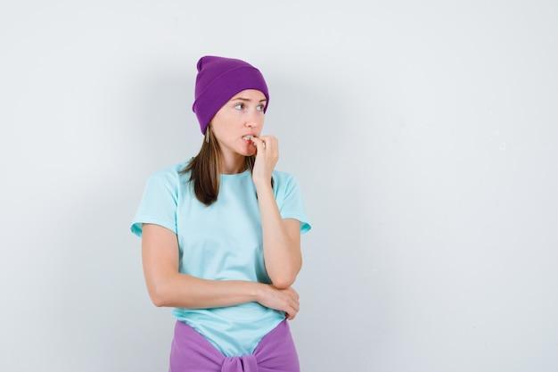 Jonge vrouw die emotioneel vingers bijt in blauw t-shirt, paarse muts en er angstig uitziet. vooraanzicht.