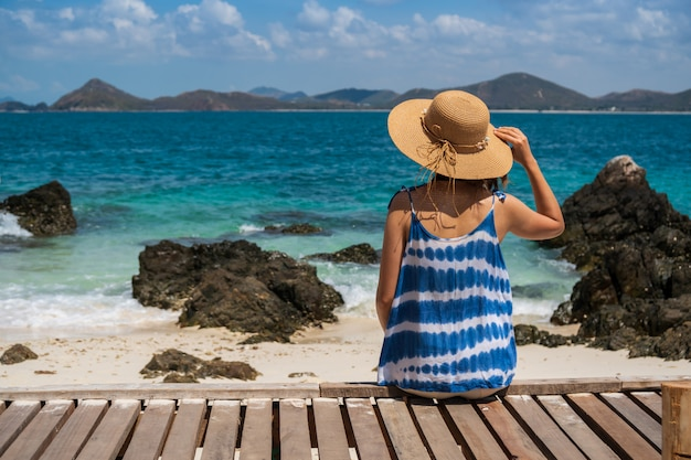 Jonge vrouw die en bij het tropische strand, de zomervakantie en het reisconcept ontspannen genieten van