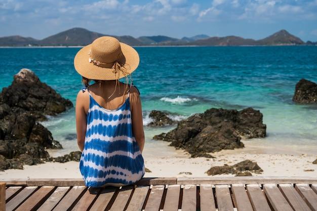 Jonge vrouw die en bij het tropische strand, de zomervakantie en reisconcept ontspannen genieten van