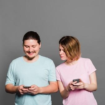 Jonge vrouw die en bij smartphone van haar vriend spioneert gluren die mobiele telefoon met behulp van