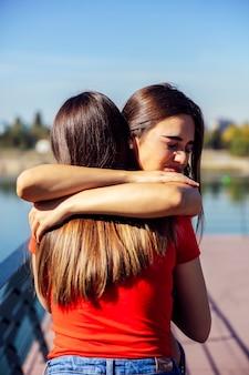 Jonge vrouw die en haar beste vrouwelijke vriend koestert steunt