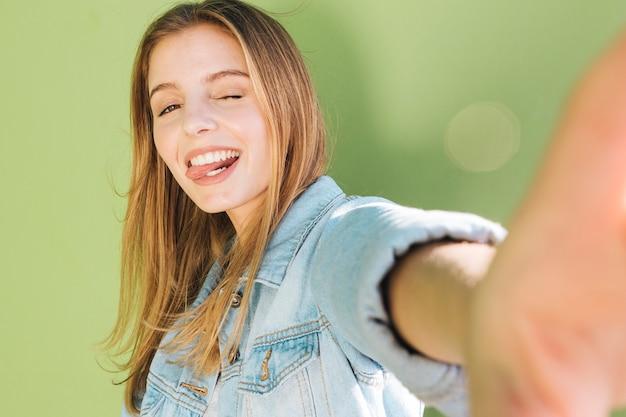 Jonge vrouw die en haar tong knipogen plakken die selfie tegen groene achtergrond nemen