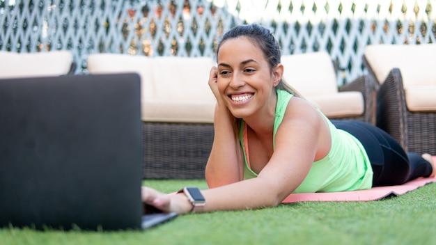 Jonge vrouw die en laptop glimlacht met behulp van terwijl zij op de tuin ligt