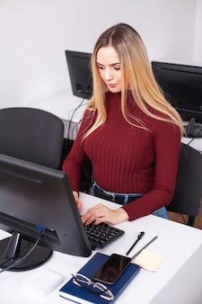 Jonge vrouw die en op computer in bureau werkt programmeert